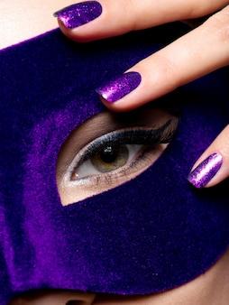 Kobiece palce z niebieskimi paznokciami wokół oka. fotografia makro