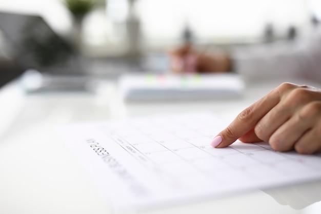 Kobiece palec wybierając datę w kalendarzu