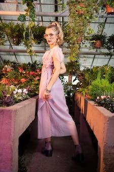 Kobiece piękno. atrakcyjna, dobrze wyglądająca kobieta dotykająca różowej sukienki, zwracając się do ciebie to