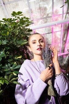 Kobiece piękno. ładna atrakcyjna kobieta patrzy na ciebie trzymając bukiet kwiatów