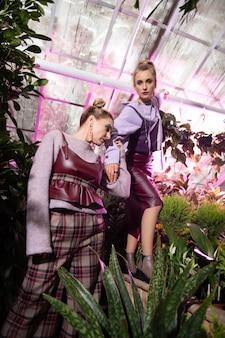 Kobiece piękno. piękne ładne modelki przebywające w ogrodzie kwiatowym podczas pracy