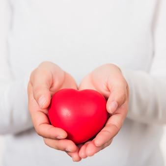 Kobiece piękno ręce trzymając nowoczesne czerwone serce