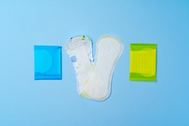 Kobiece podkładki higieniczne i tampony na niebieskim tle widok z góry