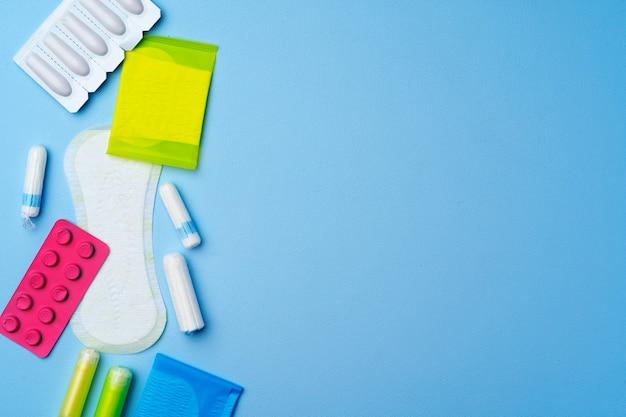 Kobiece podkładki higieniczne i tampony na niebieskim widoku z góry