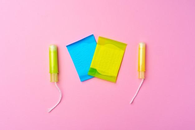 Kobiece podkładki higieniczne i tampony na różowym tle