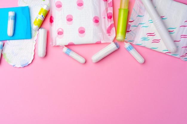 Kobiece podkładki higieniczne i tampony na różowym widoku z góry