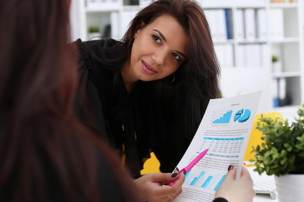 Kobiece ramię pokazuje grafikę statystyczną przypiętą do podkładki