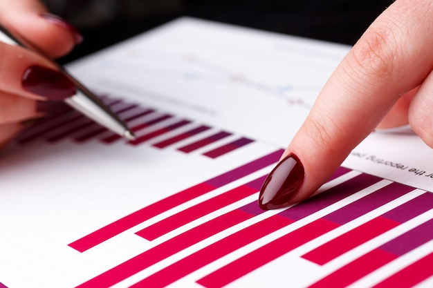 Kobiece ramię trzymać i punkt srebrny długopis na wykresie finansowym