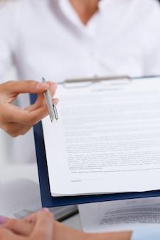 Kobiece ramię w białej koszuli oferuje formularz umowy na podkładce schowka