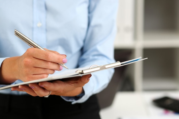 Kobiece ramię w garniturze trzyma srebrny długopis i podkładkę