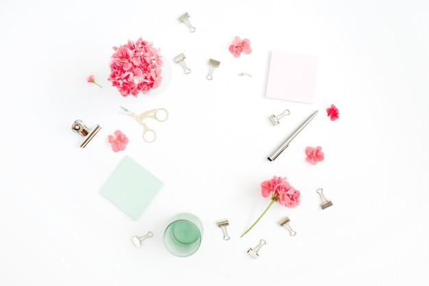 Kobiece ramka obszaru roboczego z czerwonymi kwiatami, akcesoria, pamiętnik miętowy na białym tle