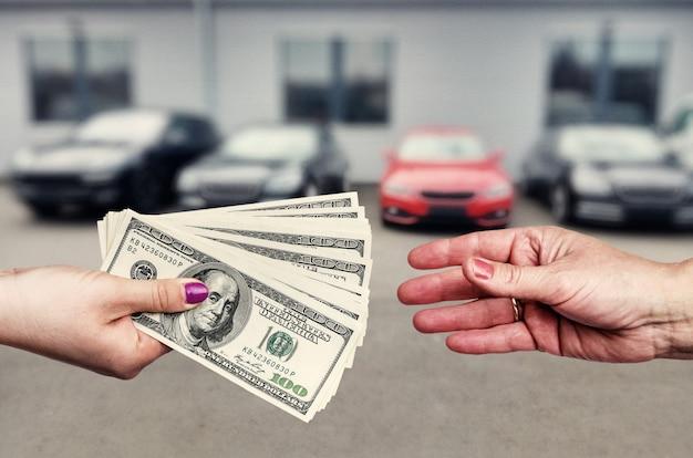 Kobiece ręce banknotami dolara na parkingu