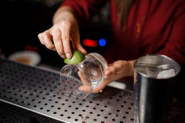 Kobiece ręce barmana tarcie szklanki soku z limonki