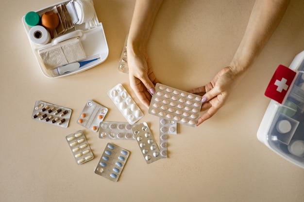 Kobiece ręce blister pigułki opakowanie pierwszy zestaw pomoc organizacja przechowywania witaminy środek przeciwbólowy dostawa lekarstwa;