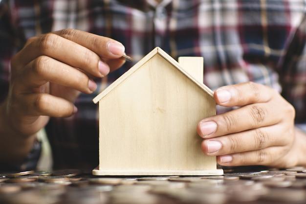 Kobiece ręce chronią mały model domu z drewna.