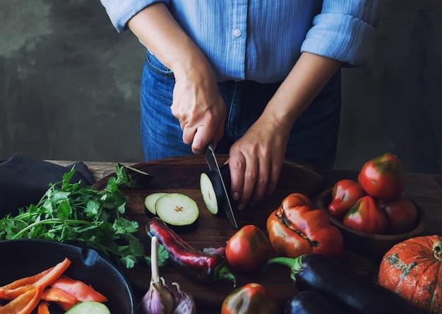 Kobiece ręce cięcia bakłażana na desce do wegańskiego jedzenia.