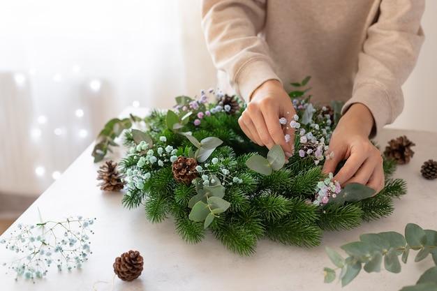 Kobiece ręce co świąteczny wieniec z kwiatami świąteczna dekoracja domu