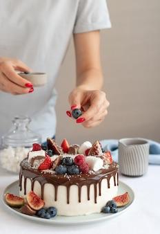 Kobiece ręce dekorowanie ciasta z jagodami przy stole w pomieszczeniu koncepcja urodziny dzień matki