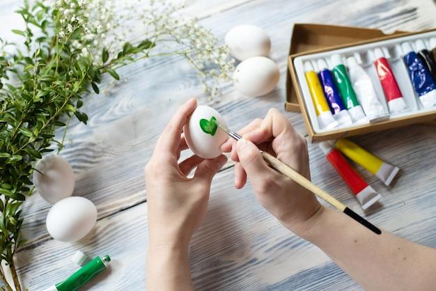 Kobiece ręce dekorowanie pisanki, rysowanie liścia na drewnianym stole, z bliska.