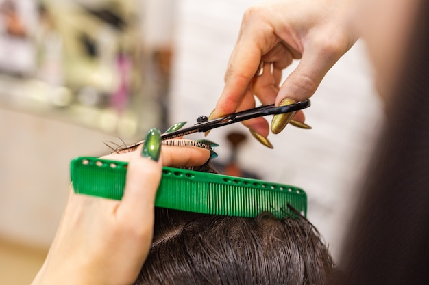 Kobiece ręce fryzjer robi fryzurę dla klienta płci męskiej za pomocą profesjonalnych narzędzi fryzjerskich nożyczki, szczotka
