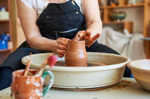 Kobiece ręce garncarza pracującego na okręgu. tradycyjne rzemiosło ludowe.