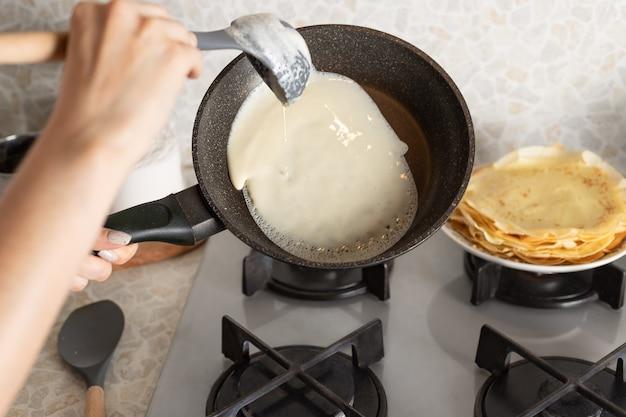 Kobiece ręce gotowanie cienkich naleśników na patelni