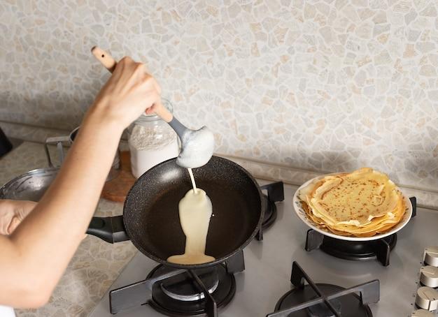 Kobiece ręce gotowanie cienkich naleśników