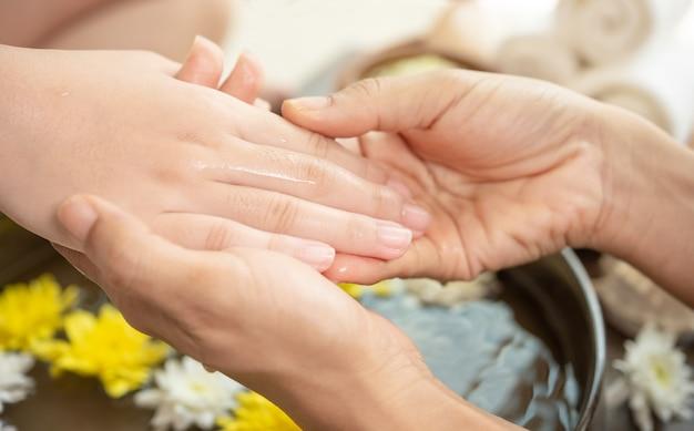 Kobiece ręce i miskę wody spa z kwiatami, z bliska. ręce spa.