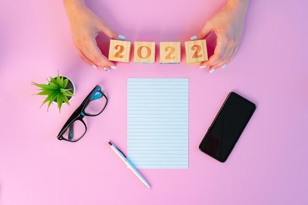 Kobiece ręce i otwarty notatnik na różowym tle
