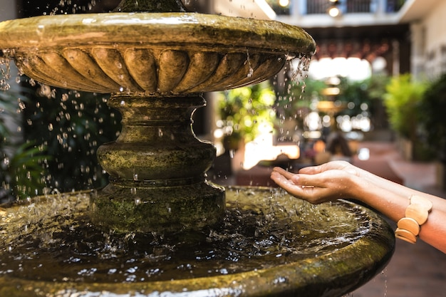 Kobiece ręce i starożytna fontanna z rozpryskiwaniem kropli wody