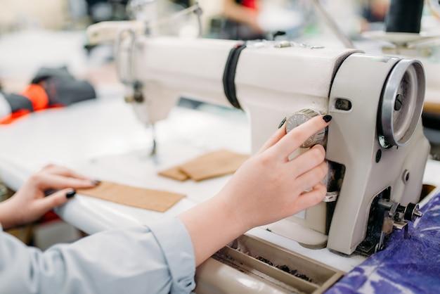 Kobiece ręce krawcowe szyje tkaniny na maszynie do szycia. krawiectwo lub krawiectwo w fabryce odzieży, robótki ręczne, krawcowa w warsztacie