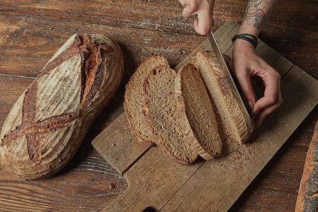 Kobiece ręce kroją ekologiczny chleb na starym drewnianym tle leżał płasko