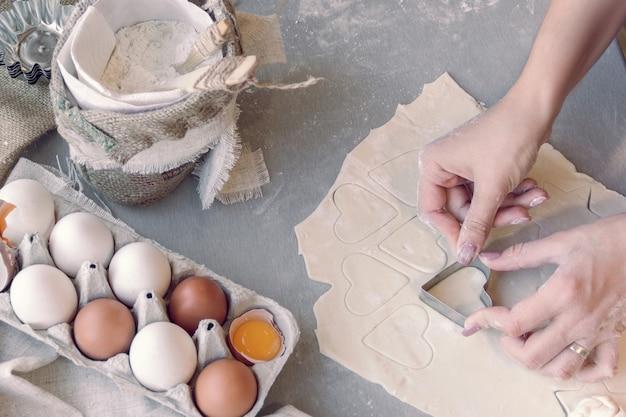 Kobiece ręce krojące ciasto blaszką w kształcie serca