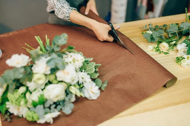 Kobiece ręce kwiaciarni tnie dekoracje kwiatowe nożyczkami. biznes kwiatowy, proces przygotowania bukietu