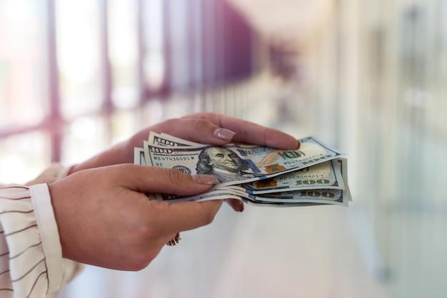 Kobiece ręce liczące banknoty dolarowe lub płacące gotówką stojące w nowoczesnym centrum biznesowym lub centrum handlowym