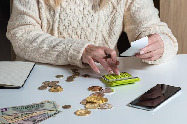 Kobiece ręce liczenia danych vat podatki kosztują, robiąc papierkową robotę w domu tabeli biurowej, z bliska