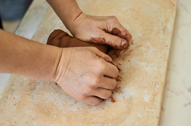 Kobiece ręce mistrza ugniatają czerwoną glinę. przygotowanie do pracy w warsztacie garncarskim.