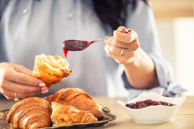 Kobiece ręce nakładają rano dżem na przekrojonego na pół rogalika.