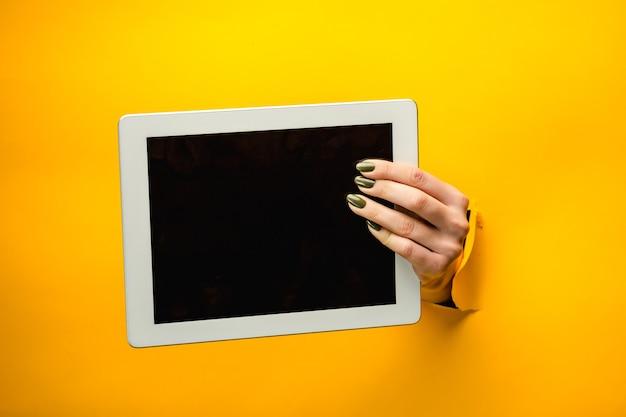 Kobiece ręce nastolatka przy użyciu komputera typu tablet z czarnym ekranem, przez rozdarty żółty papier, na białym tle