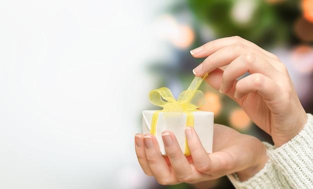 Kobiece ręce otwierają świąteczny prezent na tle choinki