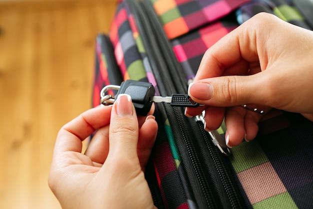 Kobiece ręce otwierają walizkę z rzeczami. koncepcja podróży