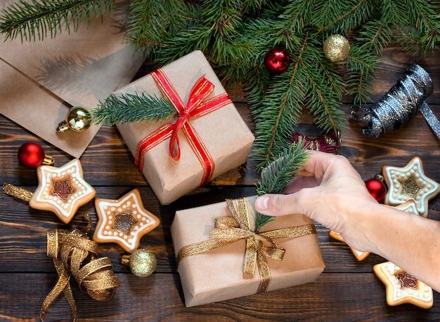 Kobiece ręce pakują prezent świąteczny na drewniany stół z domowymi ciasteczkami i zabawkami na choinkę