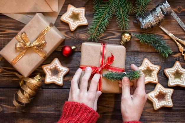 Kobiece ręce pakują prezent świąteczny na drewniany stół z gałązkami świerkowymi ciasteczkami domowej roboty i chris