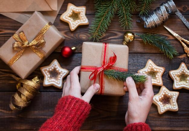Kobiece ręce pakują świąteczny prezent na drewniany stół ze świerkowymi gałązkami domowe ciasteczka