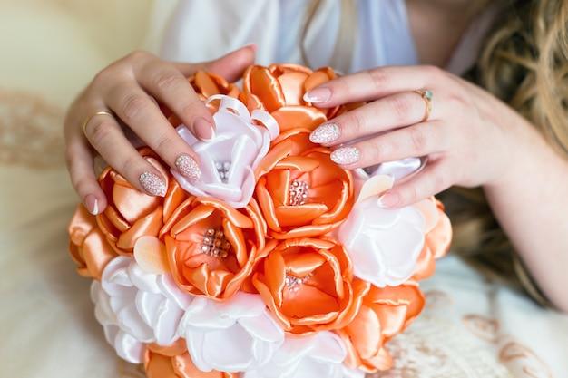 Kobiece ręce panny młodej na bukiet kwiatów z bliska.