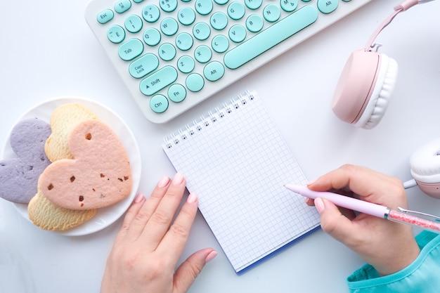 Kobiece ręce pisać piórem w zeszycie