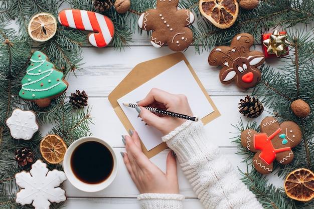 Kobiece ręce pisać powitanie kartki świąteczne na tle gengerbread i prezenty.