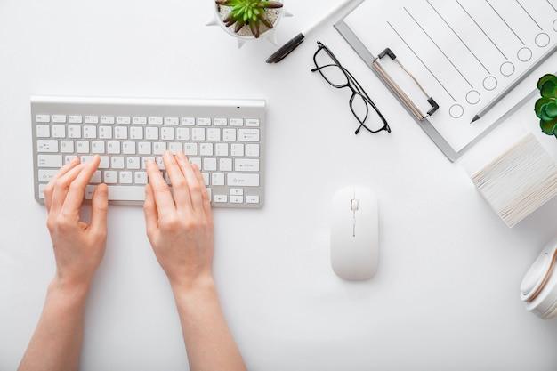 Kobiece ręce pisania na klawiaturze w miejscu pracy biały stół. obszar roboczy biura domowego z okularami z klawiaturą i myszką. płaskie leżał ręce kobiety na białym biurku używać srebrnej klawiatury komputera pc. widok z góry.