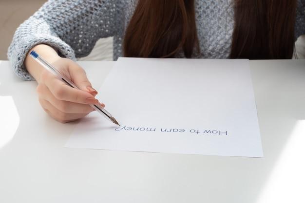 Kobiece ręce piszą na kartce, jak zarabiać