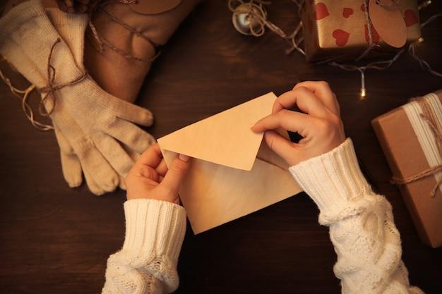 Kobiece ręce pisząc list z życzeniami świątecznymi